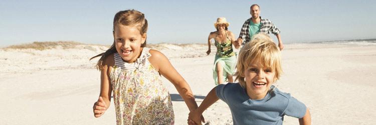 Children & parents running on the beach